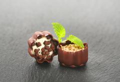 Two chocolate pralines on black background Stock Photos