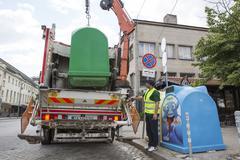 Recycling truck picking up trash bins - stock photo