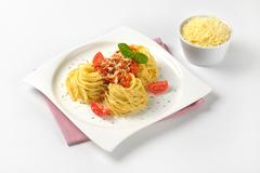plate of cooked spaghetti with tomato pesto and bowl of grated parmesan chees - stock photo