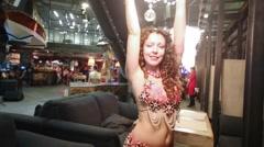 Brunette woman dancing belly dancing under chandelier in restaurant. Stock Footage