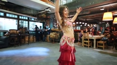Woman in red dress and adornments vigorously dancing belly dance Stock Footage