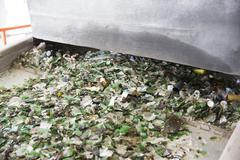 Glass waste in recycling facility. Glass particles in a machine - stock photo
