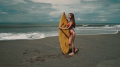 Young woman standing on black Bali beach with a surf board - stock footage
