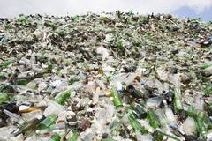 Glass waste in recycling facility. Pile of bottles. - stock photo