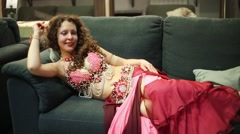 Brunette woman in red dress and beautiful jewelry lying on sofa. Stock Footage