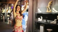 Brunette woman in dress and jewelry dancing in room with sculptures. Stock Footage