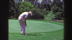 1968: Man chips golf ball from green fringe drops in hole onlooker in amazement. - stock footage