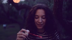 Slow motion shot of young woman having fun with soap bubbles - stock footage