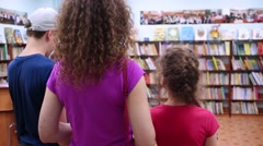 Mother with daughter and son standing in library looking at shelves Stock Footage