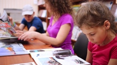 Girl reading magazine at library, and next to her mother and brother. Stock Footage