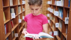 Girl reading book among bookshelf with books in library and looks up. Stock Footage