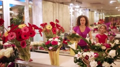 Mom and daughter considering bouquets of gerbera, roses, bells Stock Footage