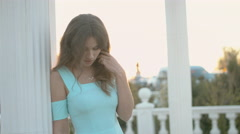 Feminine girl in the blue dress standing on the balcony near the columns at Stock Footage
