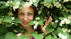 Womans face among white jasmine flowers and leaves in park. Stock Footage