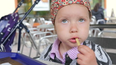Little child kid girl eating french fries potato with hands fast food restaurant - stock footage