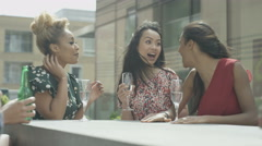 4K Happy female friends chatting & drinking on city rooftop in the summer Stock Footage