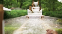 Close up of water flowing through gutters clear top down in park. Stock Footage