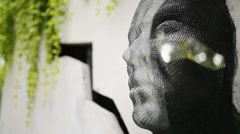 Net mask human face sticking out of wall among plants in park. Stock Footage