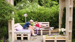 Sister with brother resting and talking in gazebo on benches Stock Footage