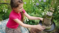 Girl sitting on chair and touching and exploring old oil lamp Stock Footage