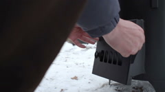 Cooking on a wood stove in the winter. A man kindling a wood stove. Stock Footage