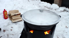 Cooking on a wood stove in the winter. Cast iron cauldron with a lid on a stove Stock Footage
