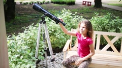 Girl looking through telescope on bench among bushes pigeonberry. Stock Footage