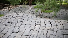 Girl going undulating stone-paved area with small trees in park. Stock Footage