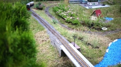 Black locomotive model with two cars going across bridge on railway Stock Footage
