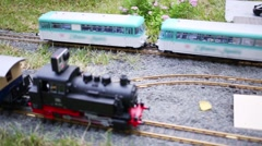 Locomotive model with action-camera on roof coming to mini station Stock Footage
