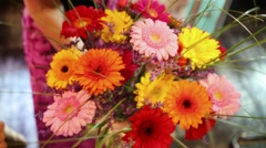 Bouquet of gerberas, limonium and bergrass in hands of woman in store Stock Footage