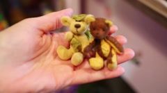 Two small teddy bear sitting on hand close up in store. Stock Footage