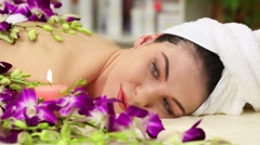 Womans face with roll up in towel hair lying among orchids Stock Footage