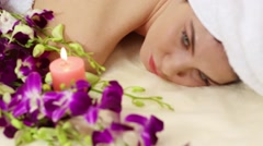Woman with white towel roll up hair lying and blinking among flowers Stock Footage