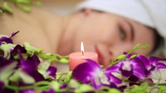 Blurred woman lying face for orchids and candle in beauty salon. Stock Footage