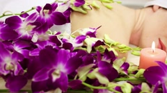 Woman lying on her belly and around orchid, and candle Stock Footage