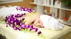 Woman lying on her belly wrapped in towel among orchids Stock Footage