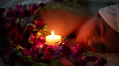 Orchids around face and shoulders of women light candles close up Arkistovideo
