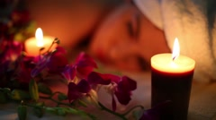 Blurred face of woman lying in flowers in light of two candles Stock Footage