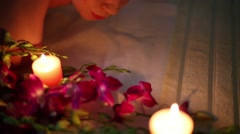 Female putting down her head rolling in towel near orchid flowers Stock Footage