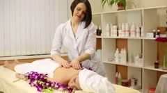 Masseuse in white coat making massage woman lying in flowers Stock Footage