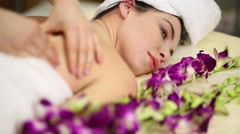 Woman on bed among orchids doing shoulder and back massage Stock Footage