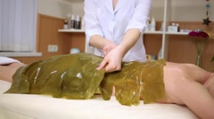Beautician correcting plate of algae on body of woman on procedure Stock Footage