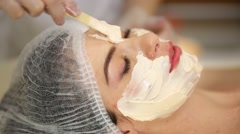 Woman with smeared face cream smearing on her forehead with stick in beauty Stock Footage