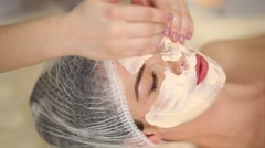 Woman hands spreading cream on her nose rubbing it in beauty salon. Stock Footage