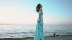 Amazing brunette in a long blue dress enjoying life near the sea - stock footage