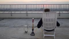 Man smoking shisha sitting chair overlooking panorama of city on roof Stock Footage