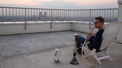 Guy sitting in chair, smoking hookah exhaling smoke Stock Footage