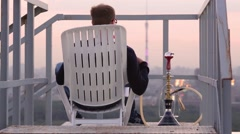Guy smoking hookah and transposing it closer, checking heating on roof Stock Footage