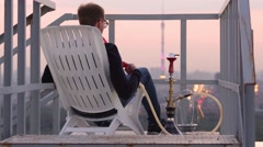 Guy sitting on chair, smoking hookah from pipe watching panorama of city Stock Footage